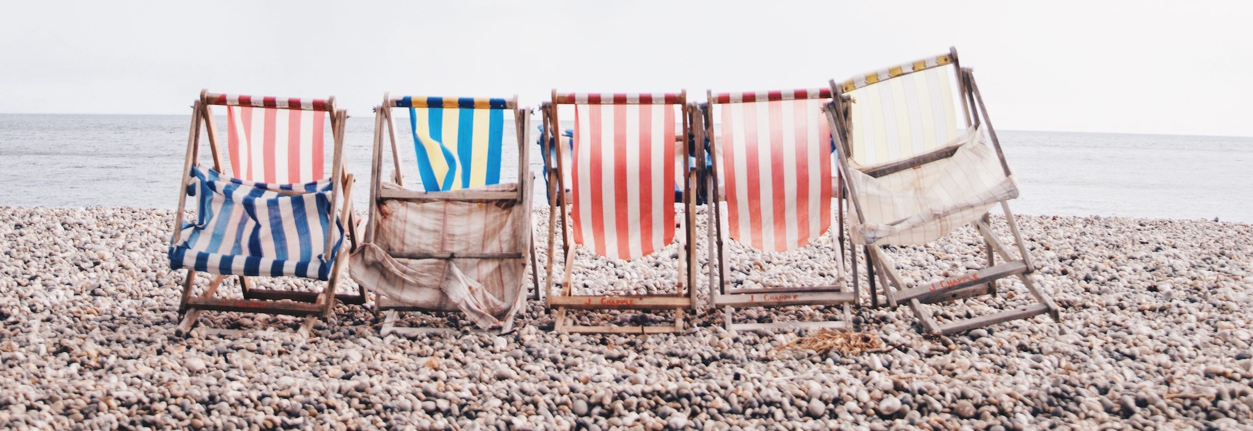 Five stripy deck chairs on the beach with the sea in the background