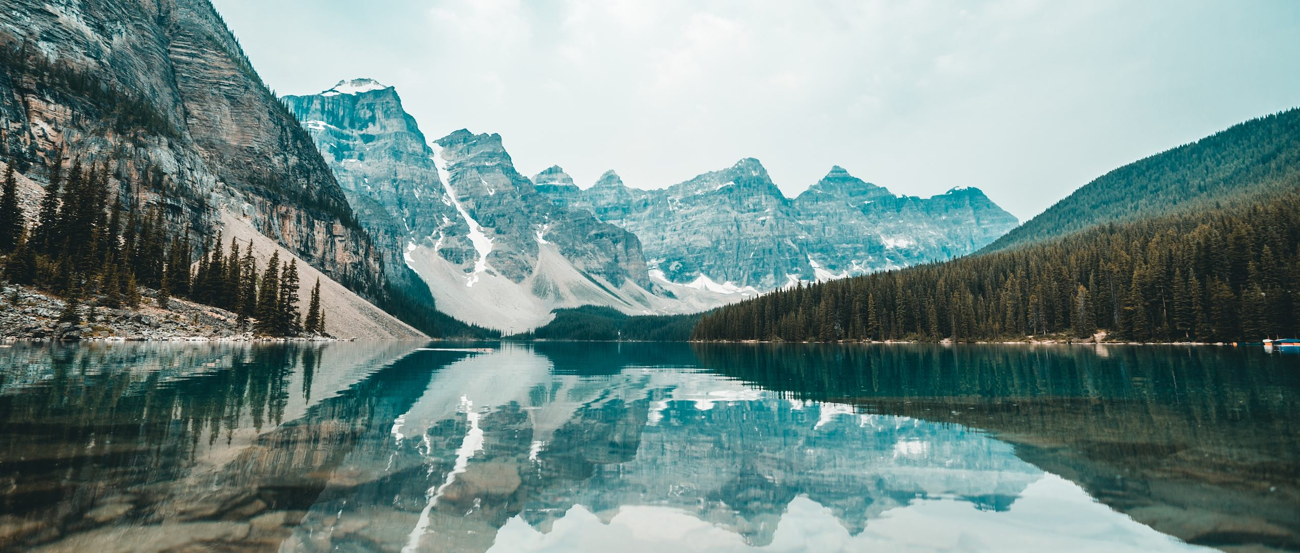 Landscape photo of a mountain lake in Canada with mountains in the background being reflected on the lake surface