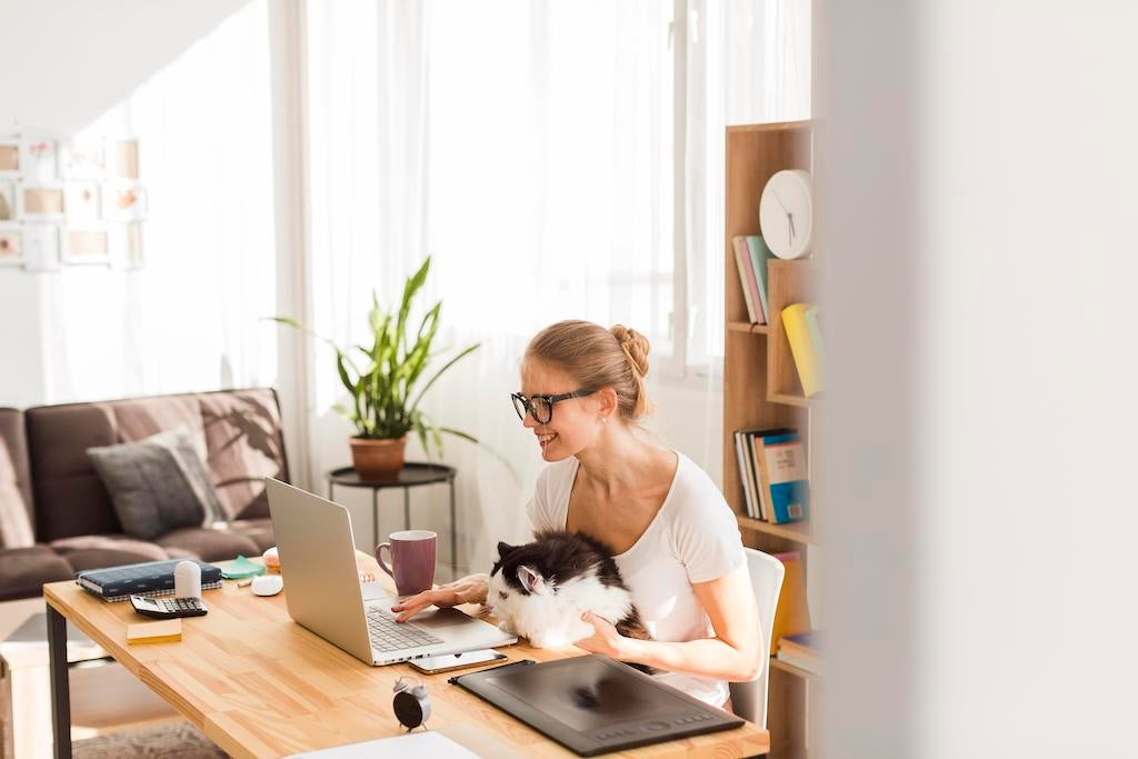 side-view-woman-desk-with-cat-working-from-home